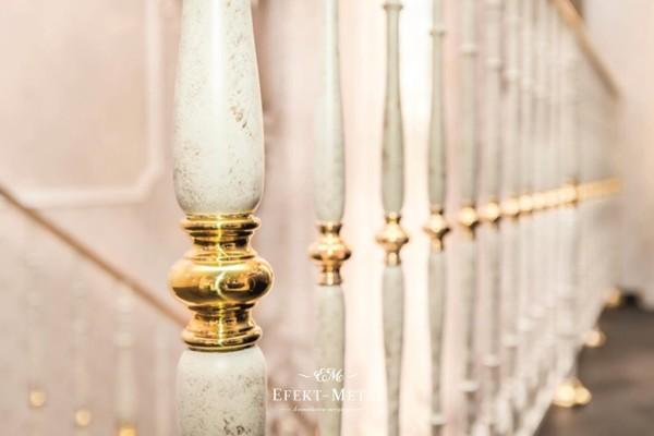 złote elementy na balustradzie kutej